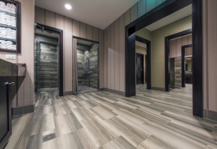 "Walls in the men's locker room showers were tiled with a combination of glass and 12"" x 24"" porcelain set using CUSTOM's ProLite® Premium Large Format Tile Mortar."
