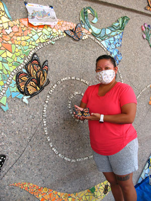 ALMA Operations Director Margarita Paz-Pedro with the in-process mural and a butterfly.