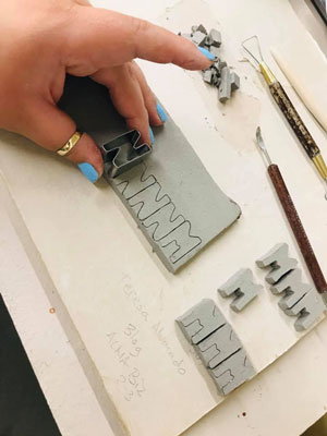 hand making letters out of clay