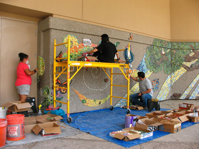(l. to r.) Margarita Paz-Pedro, Tori Lucero and Atom Vigil work on the mural installation in July.